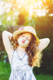 Lovely little girl in a straw hat, shaped his lips for a kiss. Royalty Free Stock Photos