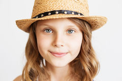 Lovely little girl with straw hat on a white background. Lovely little girl with straw hat against a white background. Closeup portrait of little girl wearing Royalty Free Stock Image