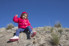 Lovely little girl throwing small stones to camera Stock Image