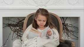 Lovely little girl wrapped in white Christmas blanket exploring a book sitting in an armchair near the decorated. Fireplace. Professional shot on BMCC RAW with Royalty Free Stock Photo