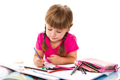Lovely little girl writing at the desk Royalty Free Stock Photos