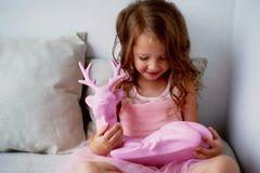 A lovely little girl 4 years old in a pink dress plays with pink deer.The atmosphere of childhood Stock Photo