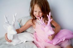 A lovely little girl 4 years old in a pink dress plays with pink deer.The atmosphere of childhood Royalty Free Stock Images