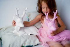 A lovely little girl 4 years old in a pink dress plays with pink deer.The atmosphere of childhood Royalty Free Stock Image