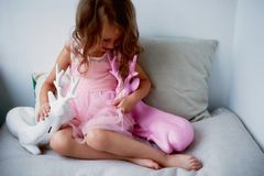 A lovely little girl 4 years old in a pink dress plays with pink deer.The atmosphere of childhood Stock Photography