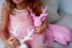 A lovely little girl 4 years old in a pink dress plays with pink deer.The atmosphere of childhood Stock Image
