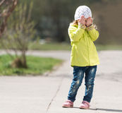 Lovely little girl in yellow coat hiding face with hands Stock Photos