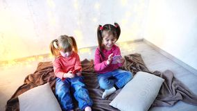 Happy little girls use smartphones for entertainment and sit on floor in bright room with garland on wall. Lovely little girls holding mobile phones and playing stock video