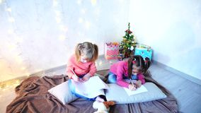Funny little girls laugh and talk, posing lying on floor and on pillows against wall with garland and Christmas tree in. Lovely little girls look at camera and stock footage