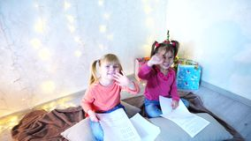 Funny little girls laugh and talk, posing lying on floor and on pillows against wall with garland and Christmas tree in. Lovely little girls look at camera and stock video footage
