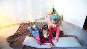 Funny little girls laugh and talk, posing lying on floor and on pillows against wall with garland and Christmas tree in. Lovely little girls look at camera and stock video