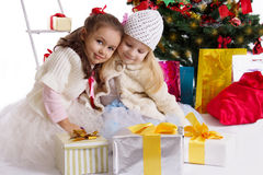 Lovely little girls with presents under Christmas tree. Two lovely little girls with presents under Christmas tree Stock Image