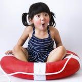 A lovely little kid playing life ring joyfully on white backgrou. Nd Royalty Free Stock Photo