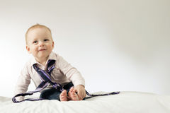 Lovely little kid with tie on his neck. Funny toddler boy in smart casual clothes with adult tie. Horizontal studio shot. Copy space royalty free stock photography
