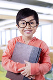 Lovely little student holding textbook in the class Royalty Free Stock Images