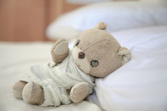 Lovely little teddy bear. It is sleeping on the bed and pillow Royalty Free Stock Photos
