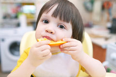 Lovely little 2 years child eats orange Royalty Free Stock Photo