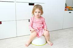 Lovely little 2 years girl sitting on potty. At home royalty free stock images