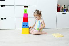 Cute 2 years toddler girl playing with educational toy at home o. Lovely little 2 years toddler girl playing with educational toy at home on the floor stock photos