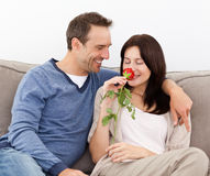 Lovely man looking at his wife smelling a red rose Stock Images
