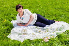 Lovely mature woman lying in the park Stock Images