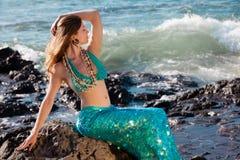 Lovely Mermaid on Lava Rocks at the Ocean Stock Images