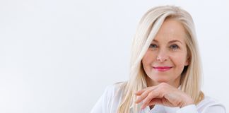 Lovely middle-aged blond woman with a beaming smile sitting at office looking at the camera royalty free stock photo