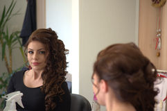 Lovely in mirror. Beautiful young woman client in a beauty salon looking in the mirror Stock Image