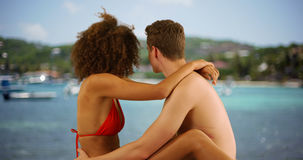 Lovely mixed race couple holding each other sitting by tropical water. Stock Image