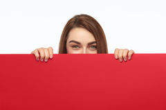 Lovely model hiding behind cardboard. Young playful girl holding big sheet of red cardboard and looking at camera on white background Royalty Free Stock Image
