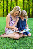 Lovely Mom and daughter Reading Outdoors Royalty Free Stock Images