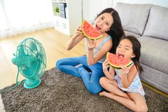 Lovely mom and kid taking a big bite of melon. Looking cheerfully and sitting together in front of electric fan. view from above royalty free stock image