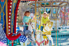 Lovely moments in funfair. Cute little sisters enjoying spring in funfair: they riding on colorful carousel and looking at camera with wide smiles stock photos