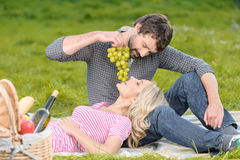 Lovely moments. Young men feeding his girlfriend with a grapes b Stock Photography