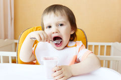 Lovely 18 months baby eating youghourt Stock Photography