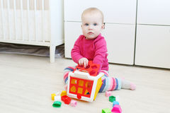 Lovely 10 months baby girl plays play educational house shape so Royalty Free Stock Photography