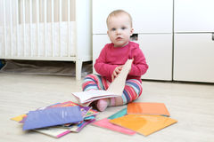Lovely 10 months baby girl reads books at home Royalty Free Stock Photo