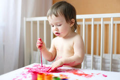 Lovely 18 months baby with paints Royalty Free Stock Photography