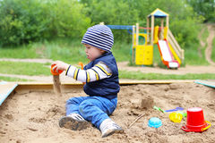 Lovely 21 months baby playing with sand. On playground in summer Stock Images