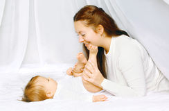 Lovely mother and baby having fun in bed Stock Image