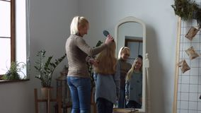 Lovely mother combing her daughter`s hair at home stock video