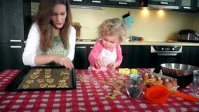 Lovely mother and daughter place cookies biscuits to oven plate tin in kitchen stock video footage