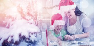 Composite image of lovely mother and daughter preparing christmas cookies Royalty Free Stock Photo