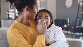 Lovely mother embracing daughter making inhalation with a nebulizer