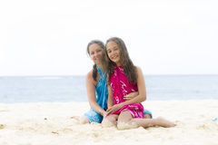 Lovely Mother and Girl Sitting on the Beach Stock Photos