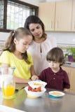 Lovely  Mother and her children having breakfast Stock Photos
