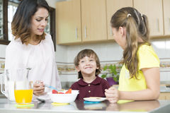 Lovely  Mother and her children having breakfast Royalty Free Stock Image