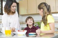 Lovely  Mother and her children having breakfast Royalty Free Stock Image