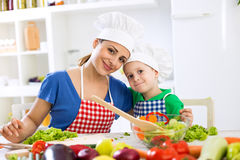 Lovely mother and kid two chefs in the kitchen Royalty Free Stock Images