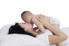 Lovely mother kissing her daughter on bed Stock Photo